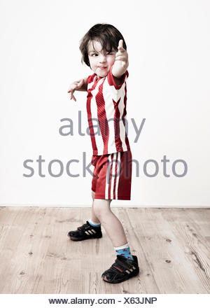 A boy in red and white striped shirt and football shorts standing pointing at the camera. - Stock Photo