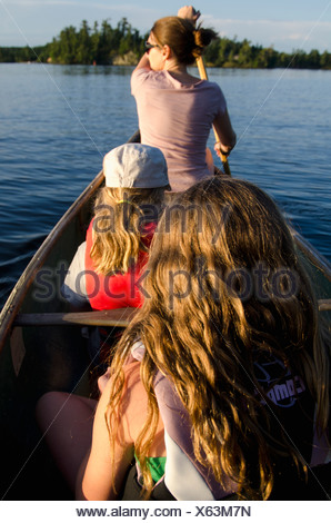 A Mother And Two Daughters In A Canoe; Lake Of The Woods, Ontario, Canada - Stock Photo