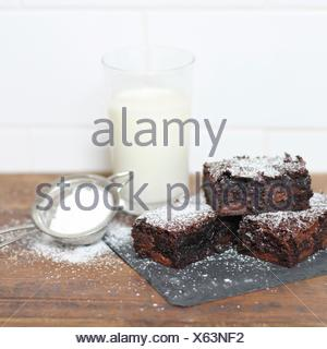 Chocolate brownies dusted with icing sugar and glass of milk - Stock Photo