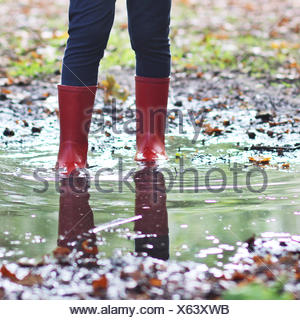 Girl wearing wellington boots standing in puddle - Stock Photo