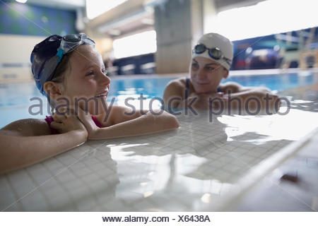 Mother and daughter swimmers bonding at edge of swimming pool - Stock Photo