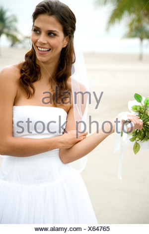 A bride standing on a beach - Stock Photo