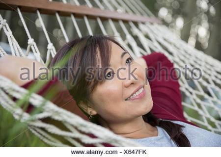 Close up smiling woman relaxing on hammock - Stock Photo