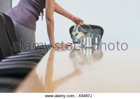 Office worker pouring water into glasses on conference table, mid section - Stock Photo