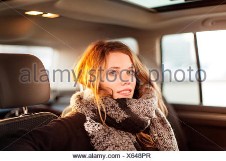 Portrait of smiling woman in a car - Stock Photo