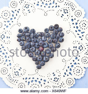 Frische Heidelbeeren in Herzform auf dekorativem Hintergrund - Stock Photo