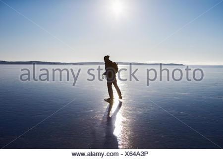 Sweden, Sodermanland, Mysingen, Silhouette of man ice-skating on frozen sea - Stock Photo