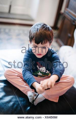 Child plays sitting on poof - Stock Photo
