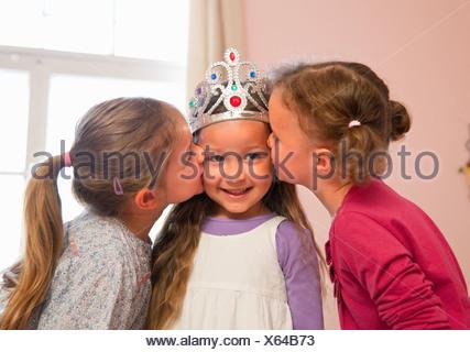 Girls kissing friend's cheeks - Stock Photo