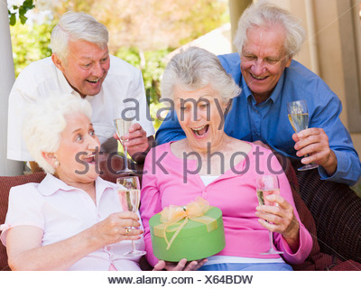 Two couples on patio with champagne and gift smiling - Stock Photo
