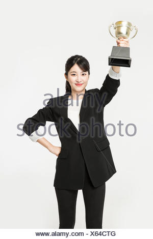 Young smiling business woman cheering with a trophy - Stock Photo