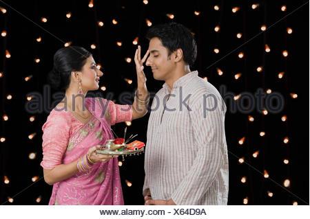 Woman doing tilak of her husband on Diwali - Stock Photo