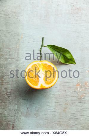 Ripe orange with leaf on textured background