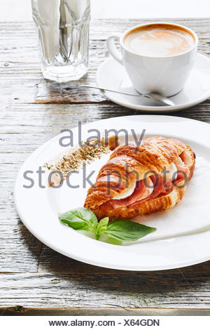 Croissant with mozzarella and ham served on white plate in a Cafe - Stock Photo