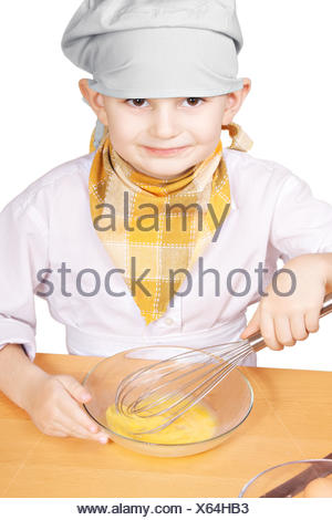 Little smiling cook whisking eggs in a bowl - Stock Photo
