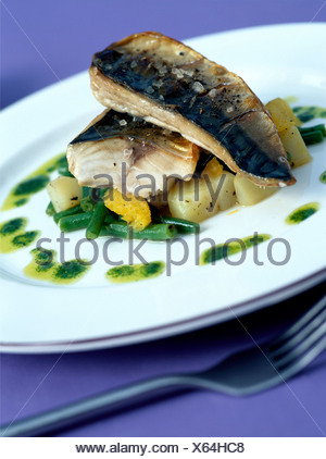 Grilled Mackerel Warm Potato Salad: Two mackerel fish fillets on diced potatoes and green beans, drizzled olive oil and herbs - Stock Photo