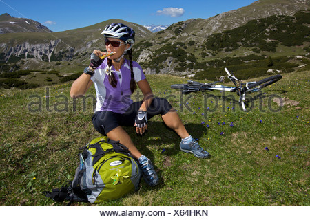 Mountain bike rider sitting on meadow with spring gentian (Gentiana verna), eating energy bar, Parco naturale Fanes-Sennes-Brai - Stock Photo