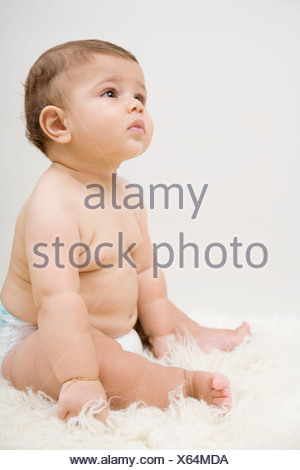 A baby boy sitting on a sheepskin rug - Stock Photo