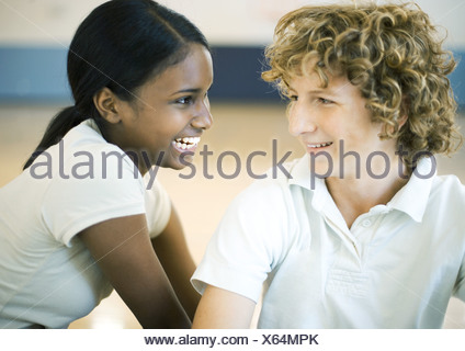 Teen couple smiling at each other - Stock Photo