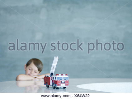 Boy dreaming behind toy firetruck - Stock Photo