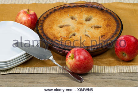 Freshly baked homemade apple pie on table cloth - Stock Photo