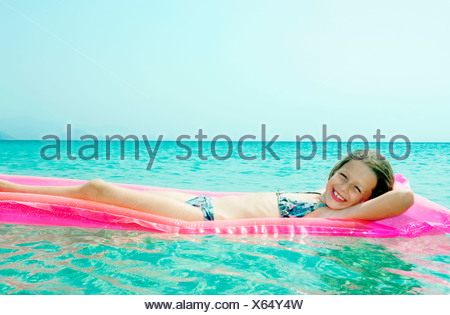 Young girl lying on inflatable raft in the water smiling. - Stock Photo