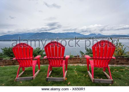... Three Red Lawn Chairs Sit In The Yard Overlooking The Lake By  Sandpoint, Idaho.