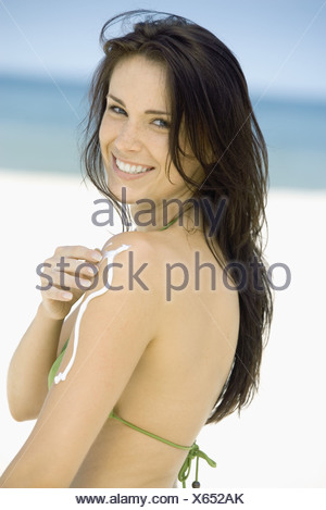 Woman applying sunscreen to arm on beach, side view - Stock Photo