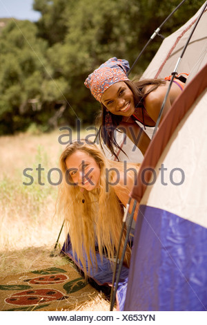 Two young women poking their heads out of a tent - Stock Photo