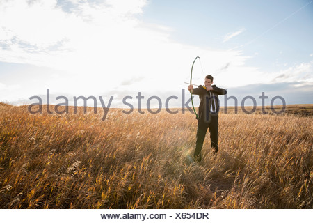 Businessman taking aim with bow and arrow in field - Stock Photo