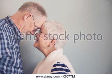 Senior couple touching foreheads and smiling - Stock Photo