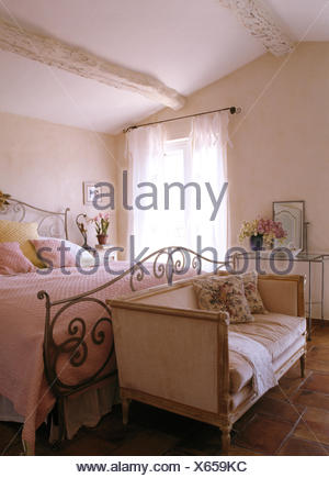 Small sofa at the foot of ornate wrought iron bed in French country bedroom - Stock Photo