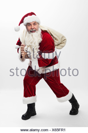 Santa carrying sack of Christmas gifts - Stock Photo