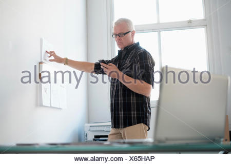 Man in office using smartphone - Stock Photo