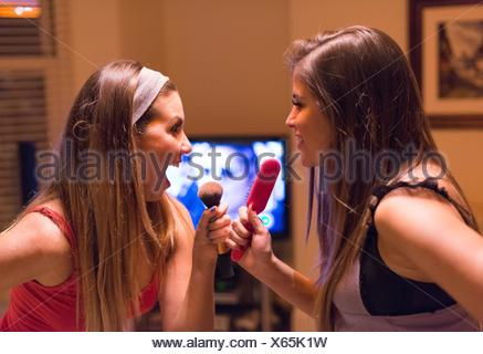 Two young women, singing into hair and make-up brushes - Stock Photo