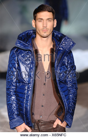 Iceberg Menswear Milan A W Brunette male wearing a shiny puffy short bright blue jacket over a brown cardigan, worn brown - Stock Photo