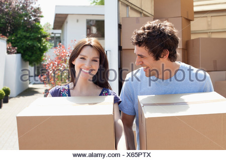Couple unloading boxes from moving van - Stock Photo