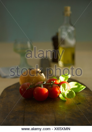 Vegetables on board with oil bottle in background - Stock Photo