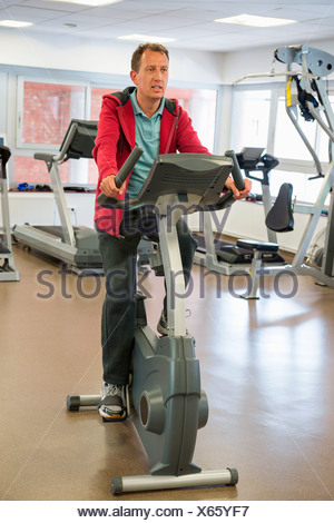 Man exercising on exercise bike in a gym - Stock Photo