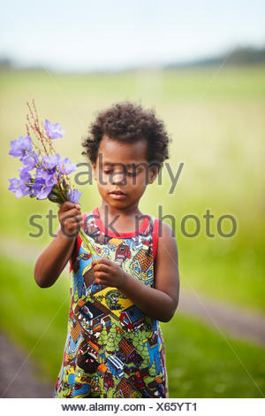 Sweden, Vastra Gotaland, Gullspang, Runnas, Girl (4-5) making bouquet - Stock Photo