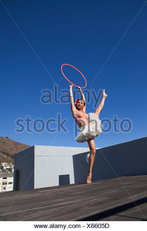 Woman in tutu dancing with hula hoop - Stock Photo