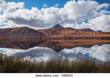 The Mountains Along The Dempster Highway Reflected In An Unnamed Pond In Autumn;Yukon Canada - Stock Photo