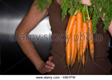 Close up of woman holding fresh carrots - Stock Photo