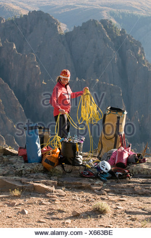 A woman coiling a climbing rope next to multiple bags of gear in the mountains of Crawford, Colorado. - Stock Photo