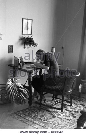 Blick auf die Inneneinrichtung eines Wohnzimmers mit einer Frau am Sekretär, Deutschland 1930er Jahre. Interior of a living room with a woman at a bureau, Germany 1930s - Stock Photo