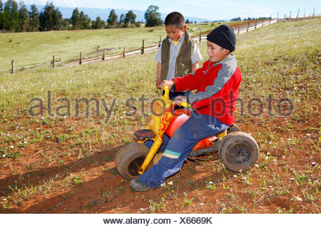 Two boys playing with a tricycle, Mapuche Indians, near Concepción, Southern Chile, Chile, South America - Stock Photo