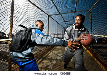 Two young guys walking down a foot bridge playing around with a basketball. - Stock Photo