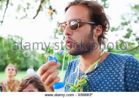 Young man blowing bubbles at sunset party in park - Stock Photo
