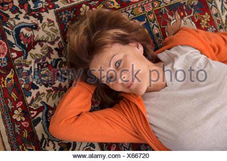 High angle view of senior woman lying on floor, Munich, Bavaria, Germany
