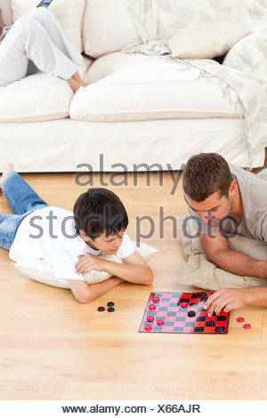 Father and son playing checkers together lying on the floor - Stock Photo